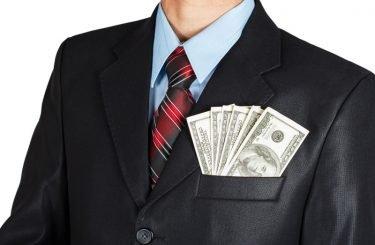 Dollars in businessman suit pocket